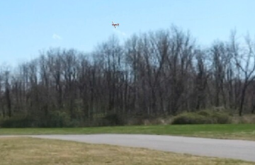 Is this plane turning in front of or behind the trees?