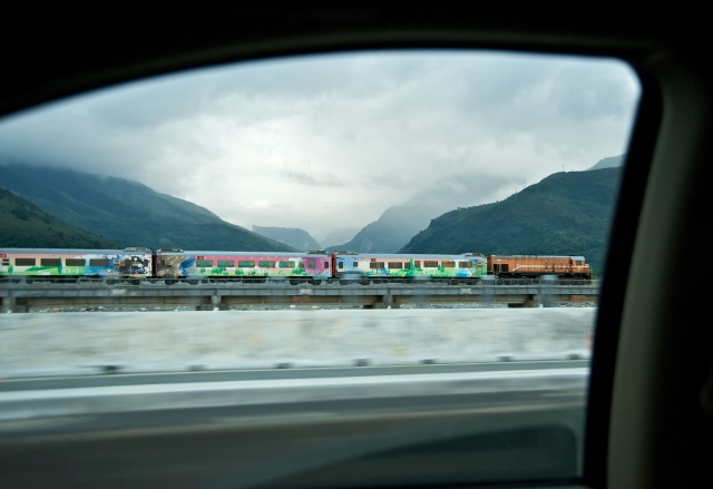 Formosa Express, a five-star tourist train, races sedans running alongside it on highway in Ji'an Township, Hualien County, Taiwan