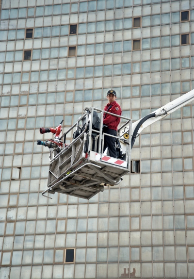 A firefighter of Taipei City Fire Department in a hydraulic platform during a fire drill.