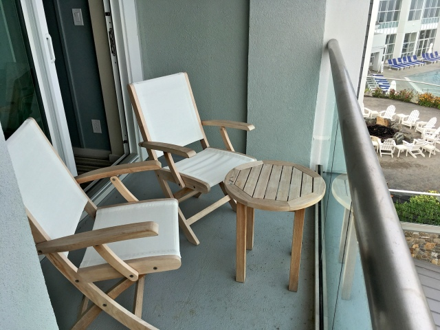 The balcony comes with two chairs and a coffee table