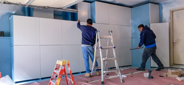 Painted cabinet doors are assembled onto frames